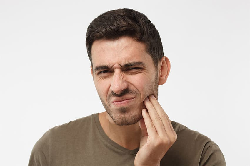 man holds the side of his face due to jaw pain