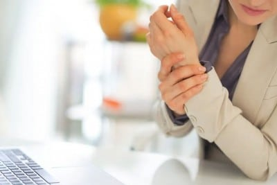 Businesswoman reacts to pain in her wrists during a busy workday