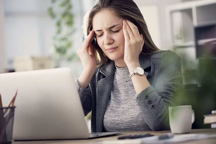 woman stressed with work closes her eyes and massages her forehead