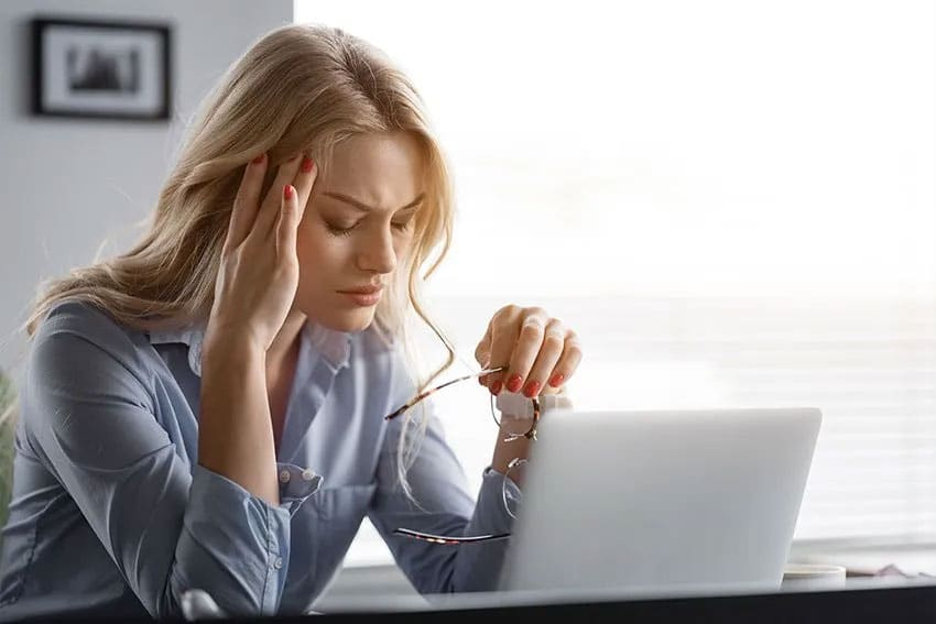 Stressed out woman takes off her eye glasses and closes her eyes during the day while working from home