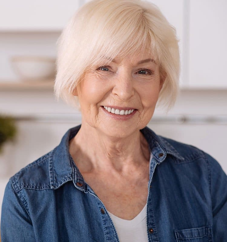 Older woman shows off her smile in her kitchen