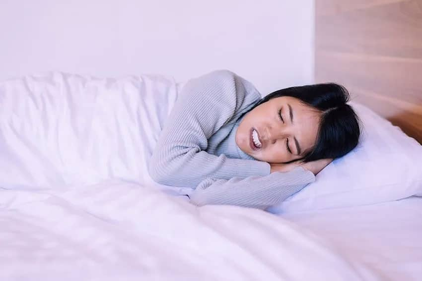 Young Asian woman grinds her teeth while sleeping in bed