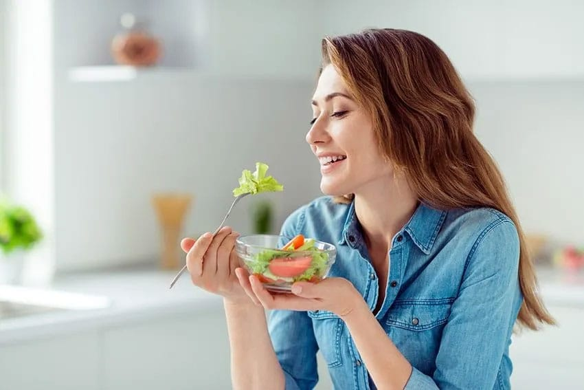 Young woman enjoying a healthy salad in her home