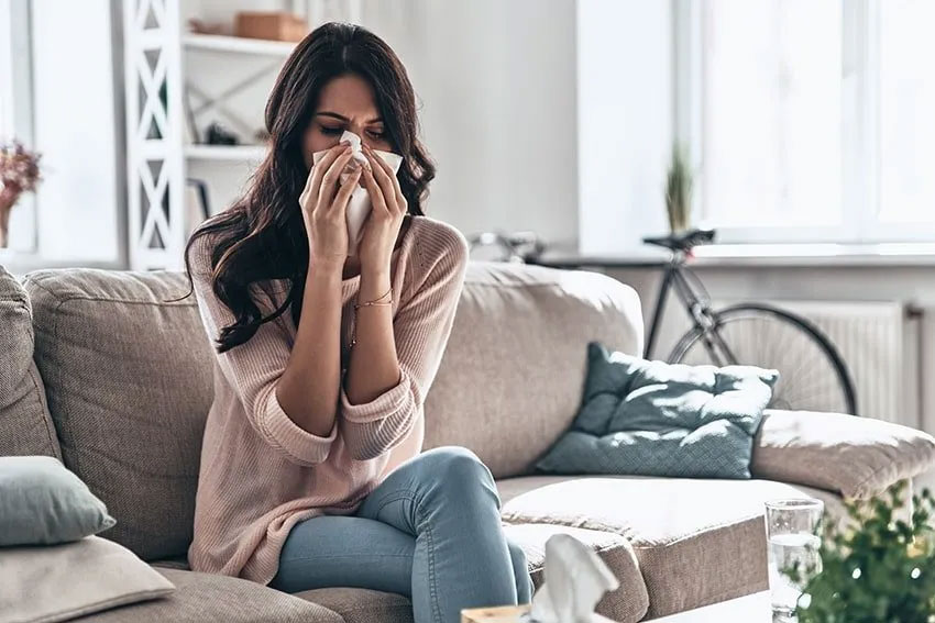woman sits on her couch, blowing her nose due to hay fever